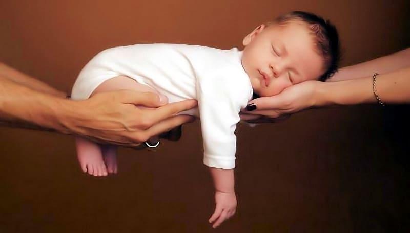 Ребенок на руках у родителей