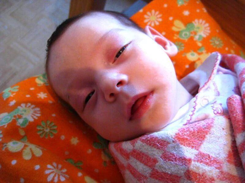 Малыш приоткрыл глаза во время сна